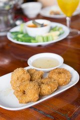 Deep-fried shrimp cakes, served on white dish and served with sweet plum sauce, Thai style appetizers, delicious Thai food.
