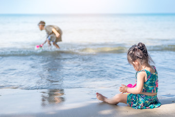 Little asian girl in swimming suite sitting, holding plastic toy, playing on the beach alone at sunrise time.