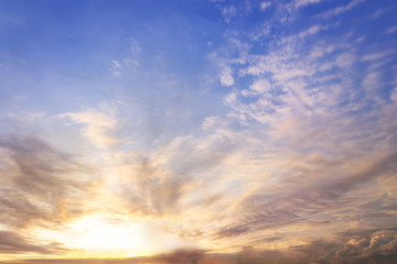 sunset / sun rise sky with rays of yellow and red light shining clouds and sky background and texture