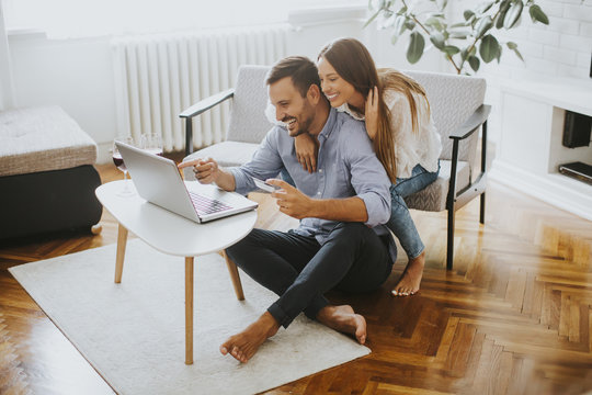 Cheerful couple searching internet on laptop at home