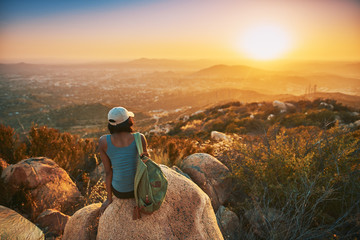 Rear view of woman hiker sitting on rock on top of hill while looking at sunset over San Diego California