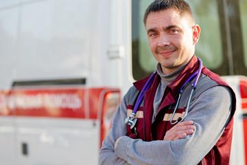 Smiling paramedic on ambulance machine background