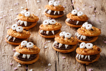 Heloween dessert: funny monsters made of biscuits with chocolate and marshmelow close-up. horizontal