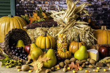 wicker cornucopia of fruit nuts pumpkins and candy corn on burlap in front of straw bale