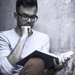 young male student reading book in old Europe city (Education, training, development, knowledge concept)