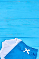 Kids summer wardrobe, copy space. Little boy cotton suit for casual wear on blue wooden background.