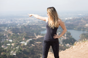 A pretty sporty young woman standing on the top of the mountain, pointing to a landmark