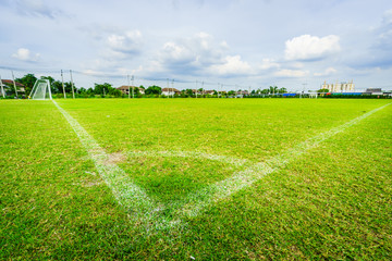 Corner of football field grass at stadium, blue sky background.