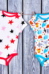 Babies rompers drying on rope. Clothesline with hanging kids bodysuits on old wooden background. Childs garment in laundry.