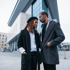 Stylish pedestrian couple. African American youth on urban background. Young fashionable models, beauty concept