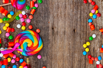 Colorful candies borders on rustic wooden background with copy space