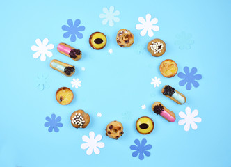 Delicious various pastries on trendy blue background.