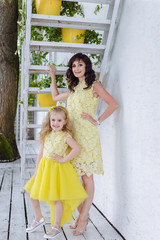 Happy loving family. Mother and her daughter child girl playing and hugging in yellow dresses