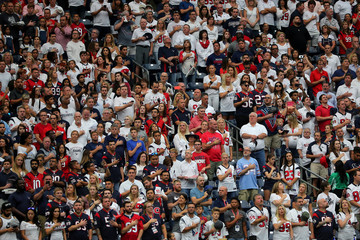 Football fans pause during  the national anthem at the Houston Texans NFL football game following the aftermath of tropical storm Harvey in Houston, Texas