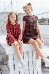 Two stylish happy beautiful fashionable girls wear in red