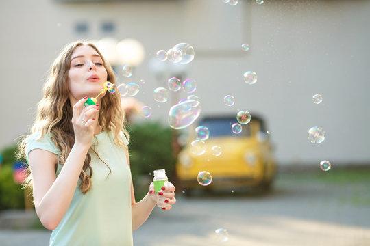 happy woman blowing soap bubbles
