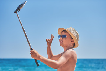 Caucasian boy making photo with selfie stick while being on the beach.