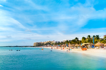 Sandy beach in the High Rise hotel area, Aruba. Unrecognisable tourists enjoy swimming and sunbathing.
