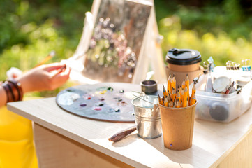 pencils in a paper cup on the table, in the background the artist draws a picture