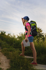 Teenager traveler with backpacks climbs the mountain. Wanderlust travel concept