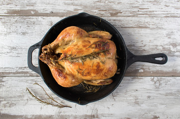 top view of baked chicken in cast iron skillet with rosemary