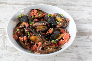 bowl of mussels with herbs and tomatos in white rustic background