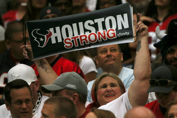 A football fan holds up a sign as she attends the Houston Texans NFL football game following the aftermath of tropical storm Harvey in Houston, Texas,