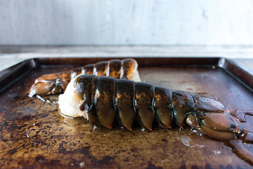 two raw uncooked lobster tails in rustic setting