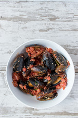 bowl of mussels with herbs and tomatos in white rustic background top view