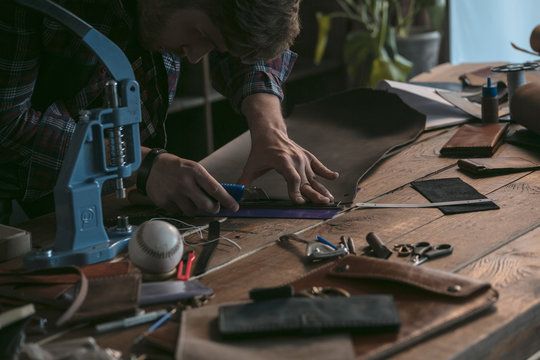 Young man carves on wooden table new piece of leather. Leather manufacturer