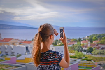 This is a view of woman with smartphone in her hand. September 3, 2017. Krk, Croatia.