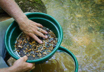 Gold panning and gem mining. Classify soil, pebbles and dirt to prepare to pan for gold and gemstones. Fun and adventure, recreational activity.