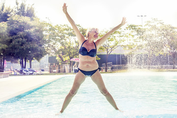 beautiful mature woman in swimsuit makes gymnastics