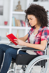 young woman reading book in wheelchair
