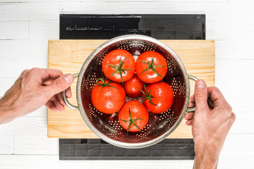 Stainless Steel Colander with Wet Tomatoes in a Chefs Hands After Washing Top View. Cooking Process Concept. Bright Kitchen Background