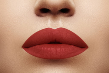 Cosmetics, makeup. Bright lipstick on lips. Closeup of beautiful female mouth with red lip makeup. Clean skin model