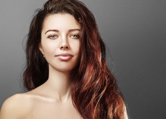Beautiful young woman with luxury hair style and fashion gloss makeup. Beauty closeup sexy model with long volume hair