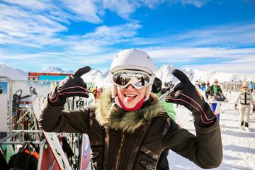 Young beautiful caucasian woman in fashionable sport jacket having fun on a ski resort.