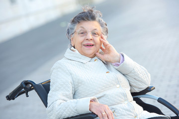 old woman in wheelchair outdoors smiling