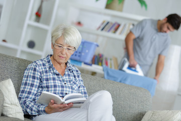 home help man ironing and senior lady reading a book