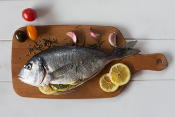 Mediterranean fish - dorado and vegetables on the chalkboard. top view