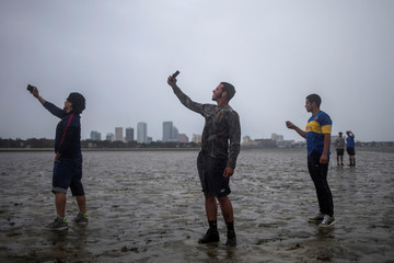 The Tampa skyline is seen in the background as local residents take photographs after walking into Hillsborough Bay ahead of Hurricane Irma in Tampa