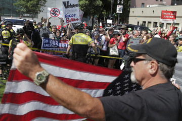 David Machado waves an American flag in a secure area as counter protesters look on in Portland
