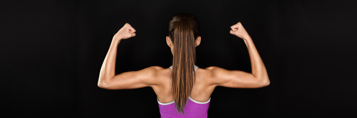 Strong fitness woman showing back and biceps muscles strength. Fit girl fitness model isolated on black background banner panoramic crop for copy space.