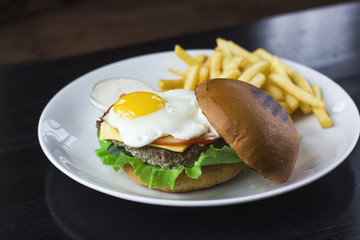The Meat Burger with egg, sauce and fries