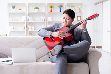 Businessman playing guitar at home