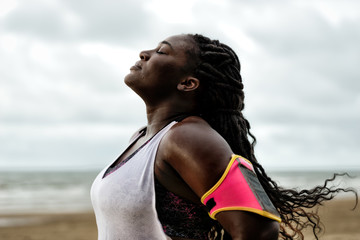 african woman standing under the rain,eyes closed, after workout on beach