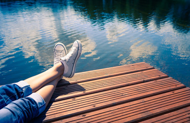 Peaceful  summer holiday. woman on wooden dock relaxing lake side.