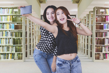 Asian students taking selfie photos in the library