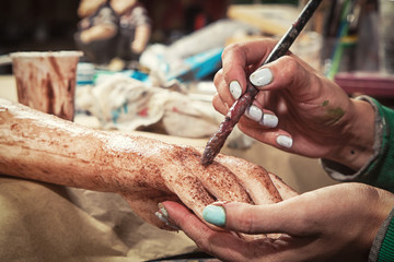 Preparing for Halloween, close-up as a young woman paints an artificial zombie hand for the quest, Halloween, fear room in the workshop